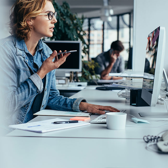 stockphoto woman with glasses on phone at computer