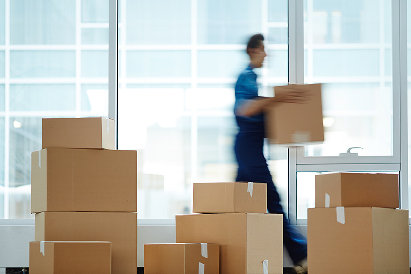 stockphoto blurred man walking past boxes carrying a box