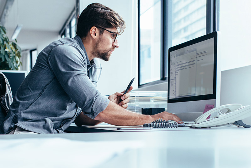 stockphoto caucasian man with glasses working at computer