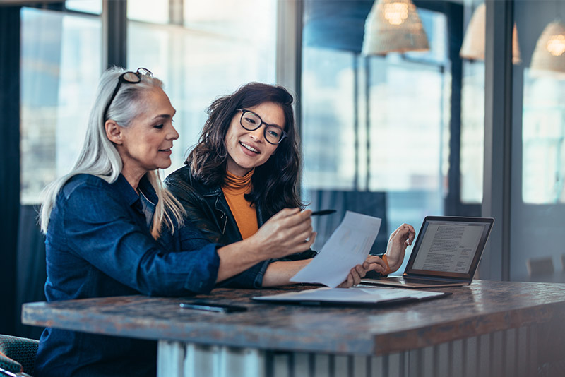 stockphoto two women at counter comparing notes