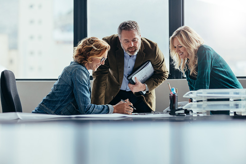 stockphoto man and two women talking at business meeting